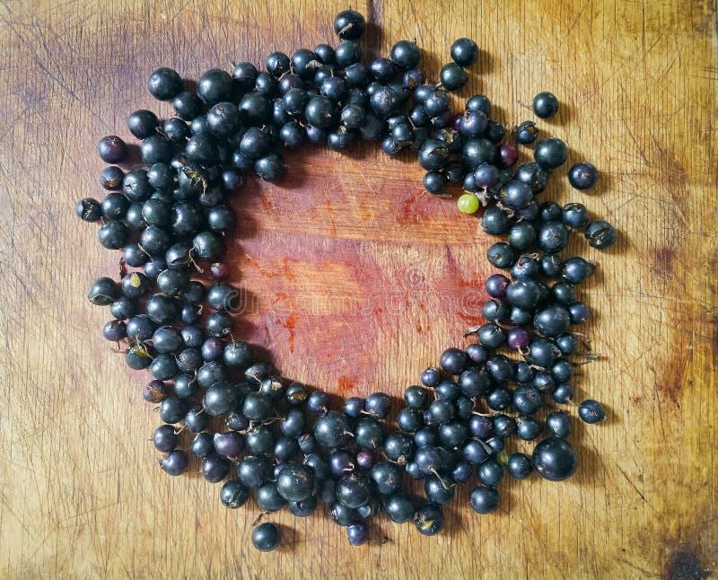 Vele zwarte bessen op een houten lijst in de vorm van een cirkel royalty-vrije stock afbeeldingen