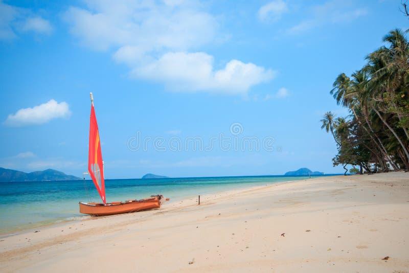 Veleiro alaranjado na praia imagem de stock