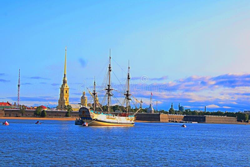 Veleiro com as velas abaixadas amarradas perto da costa da fortaleza de Peter e de Paul em St Petersburg fotos de stock royalty free