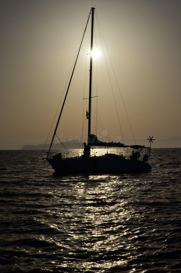 Veleiro com o moinho de vento que cruza o sol imagens de stock