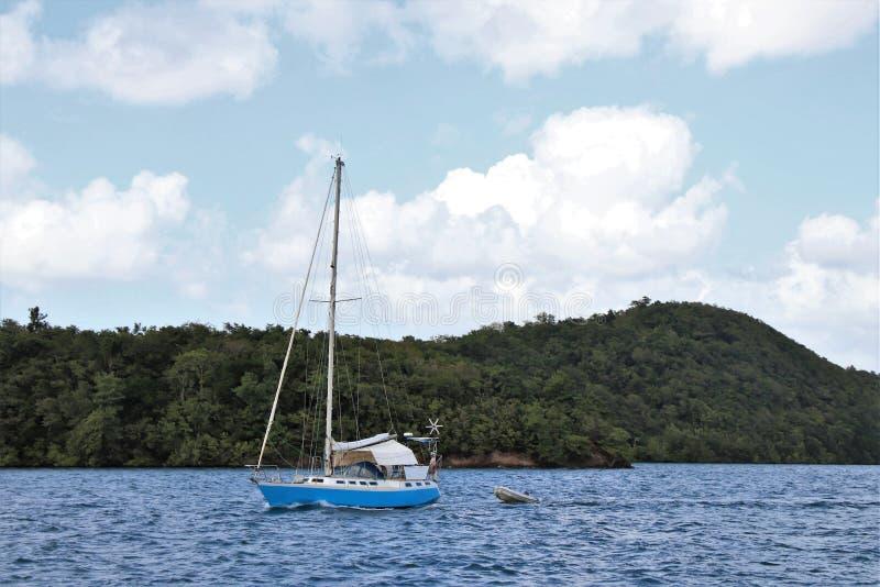 Veleiro no oceano com um céu azul bonito e um fundo branco inchado da nuvem imagem de stock royalty free