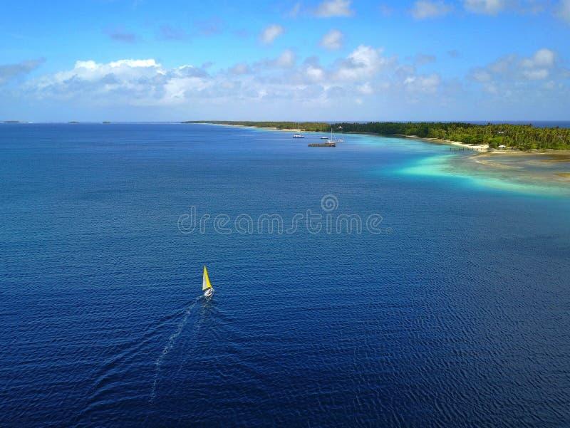 Veleiro pequeno que cruza avante em um atol tropical pristine fotografia de stock