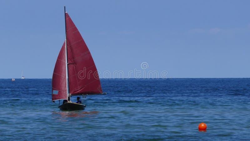 Veleiro pequeno, um bote velho da navigação com obscuridade - as velas vermelhas flutuam no mar azul fotos de stock royalty free