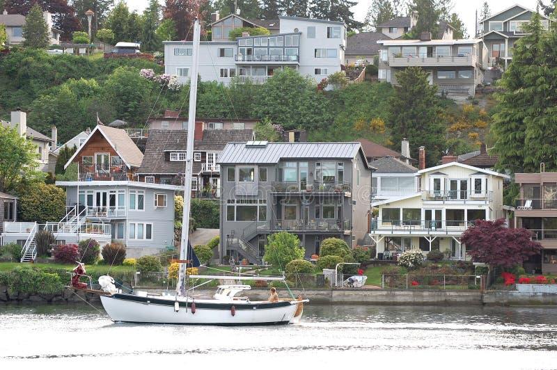 Veleiro que passa casas no canal de navio, Seattle, Wa imagens de stock