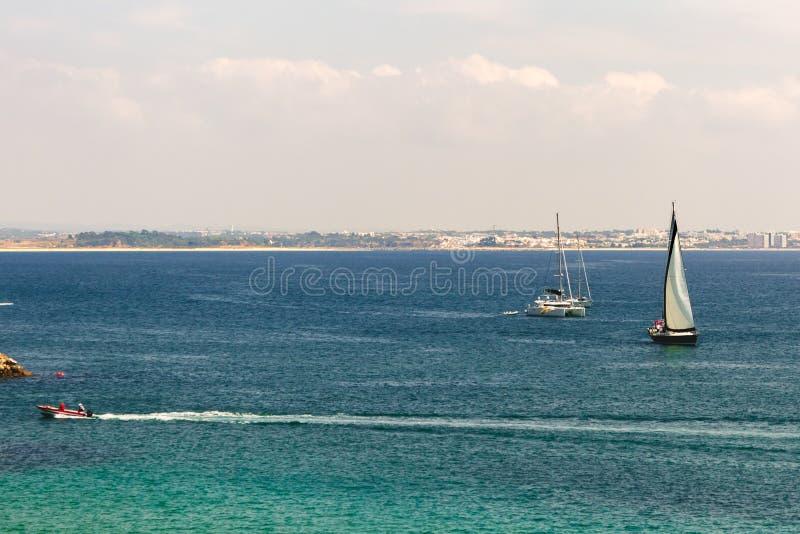 Veleiros, catamarã, e navigação do barco de motor no oceano perto de t imagens de stock