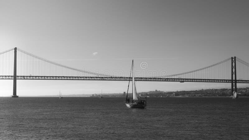 Veleiros com as velas brancas no Tagus River, 25 de April Bridge, Lisboa, Portugal - monocromático imagens de stock royalty free
