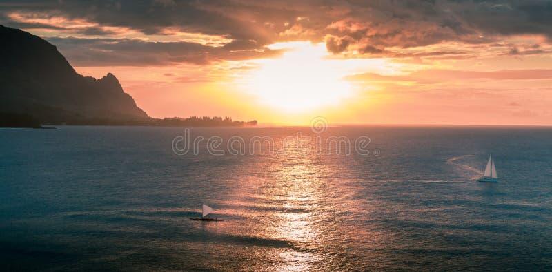Veleiros que navegam durante o por do sol na costa de Havaí imagem de stock