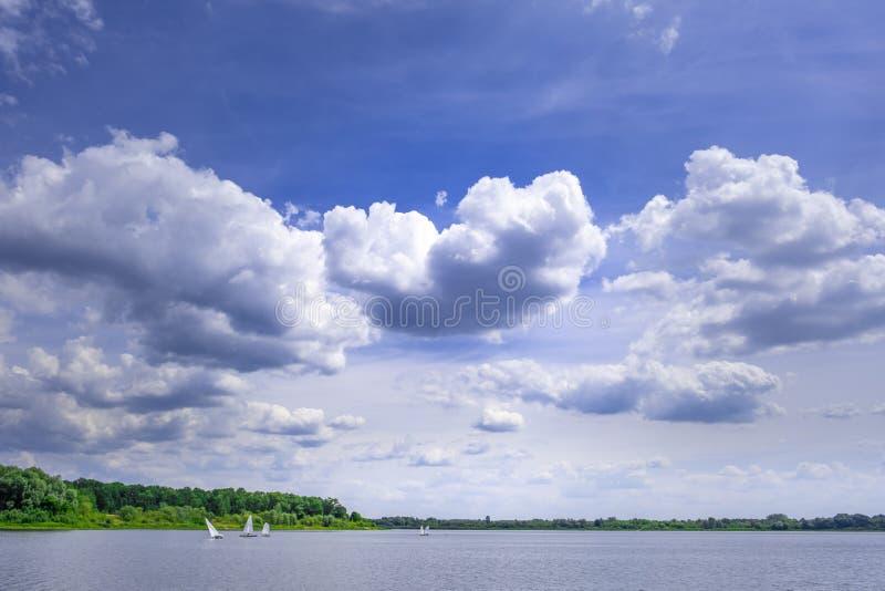 Veleiros que navegam em um rio sob o céu bonito imagens de stock royalty free