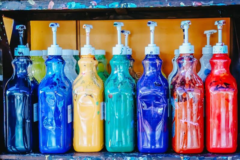 Velen fles plakkaatverf op de planken voor studenten aan praktijktekening in klasse stock fotografie