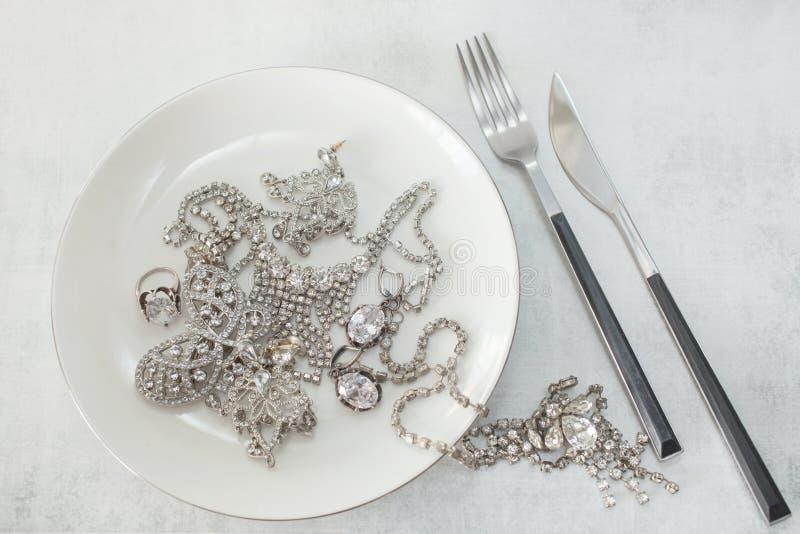 Velen fonkelende valse diamantjuwelen op een plaat met een mes en een vork Het concept het luxeleven, rijkdom, glamour royalty-vrije stock afbeelding