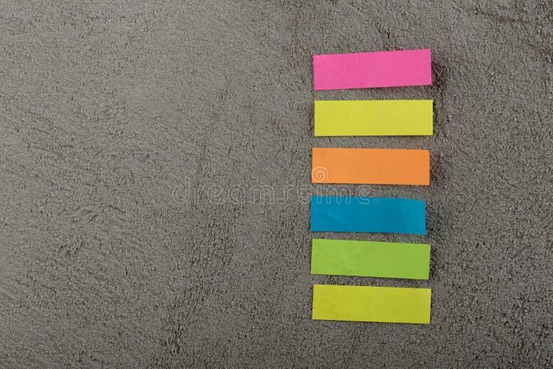 Velen kleurrijke kleverige nota over grijze cementachtergrond De ruimte van het exemplaar stock afbeelding