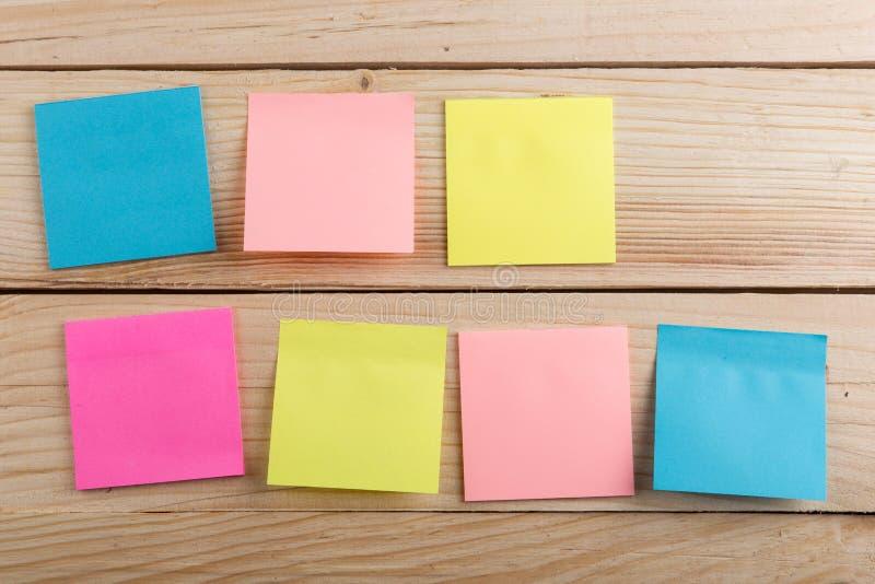 Velen kleurrijke kleverige nota over houten bureau De ruimte van het exemplaar royalty-vrije stock afbeelding