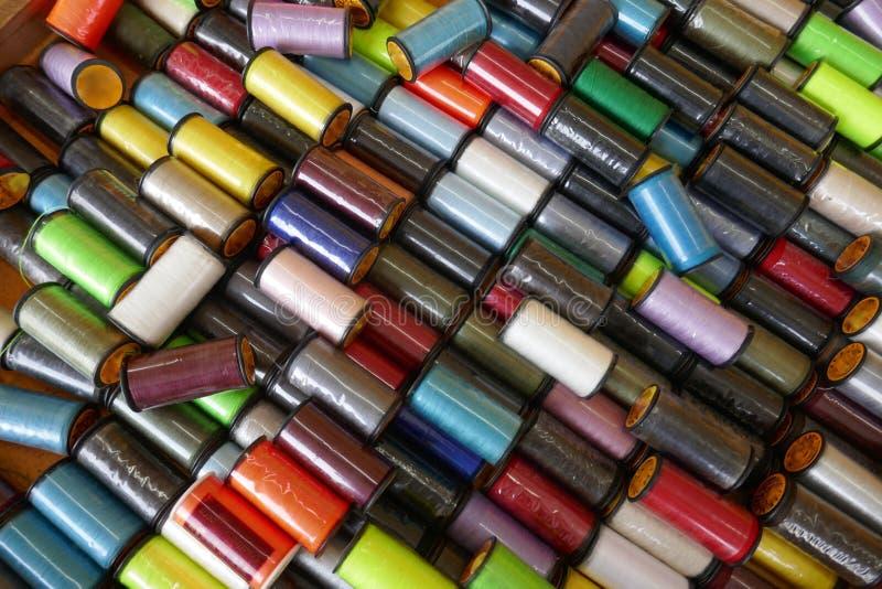 Velen kleurrijke originele ingepakte naaiende draad rollen, close-up, achtergrond, formaat het vullen royalty-vrije stock fotografie