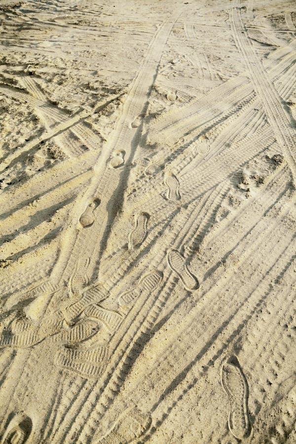 Velen vermoeien sporen en voetafdrukken in verschillende richtingen op het strandzand royalty-vrije stock foto