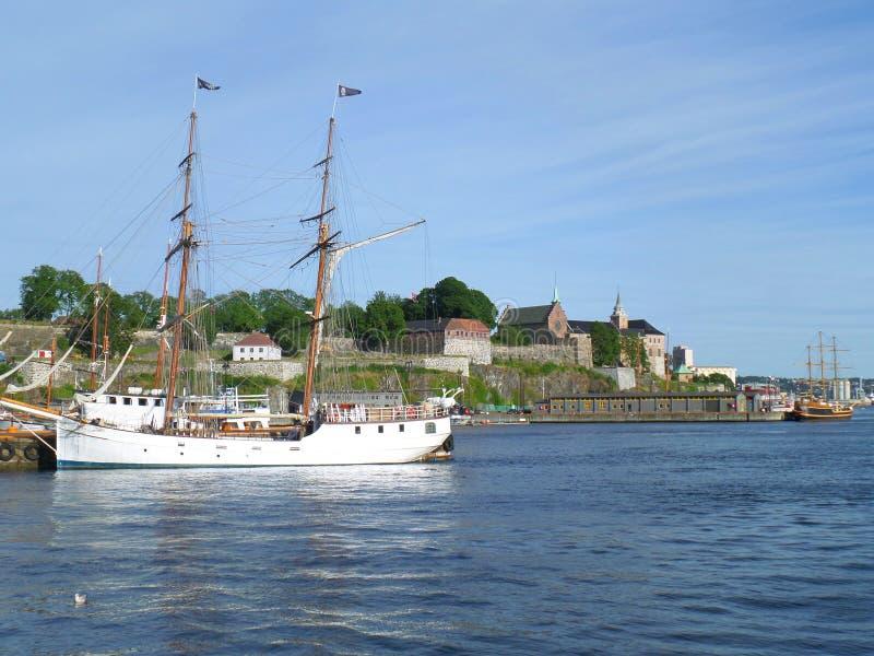 Velero blanco contra la fortaleza de Akershus, puerto de Olso imagenes de archivo