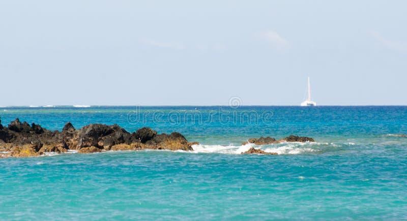 Velero blanco en aguas entre la bahía de Wailalea y Hapuna imagen de archivo