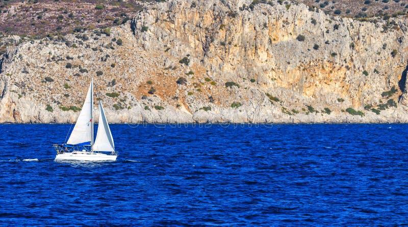 Velero blanco en el mar abierto el día soleado Yate de la navegación en el mar abierto con las montañas en el fondo lugar a fotos de archivo