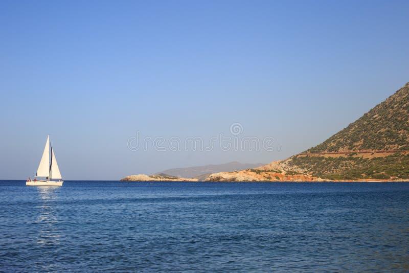 Velero blanco en el mar abierto Yate de la navegación en el mar abierto con las montañas en el fondo fotografía de archivo