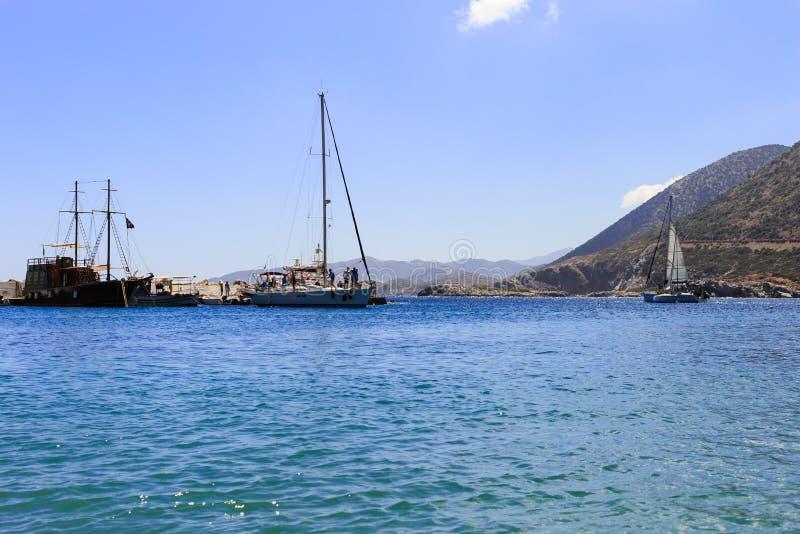 Velero blanco en el mar abierto Yate de la navegación en el mar abierto con las montañas en el fondo imagen de archivo libre de regalías
