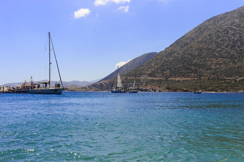 Velero blanco en el mar abierto Yate de la navegación en el mar abierto con las montañas en el fondo foto de archivo