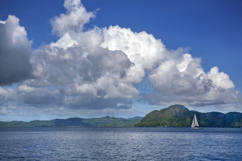 Velero en el fondo de pequeñas montañas Las nubes grandes no hacen cielo, paisaje hermoso imagen de archivo