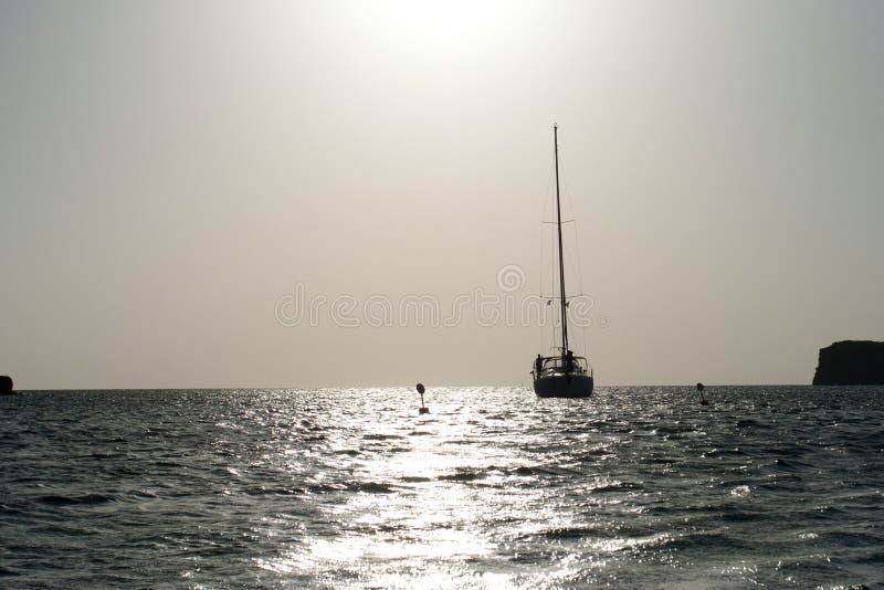 Velero en el mar en la puesta del sol