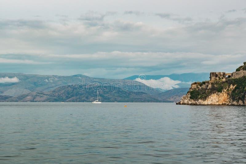 Velero en el mar en la luz del sol sobre las montañas grandes hermosas fondo, aventura del verano, vacaciones activas adentro fotos de archivo libres de regalías