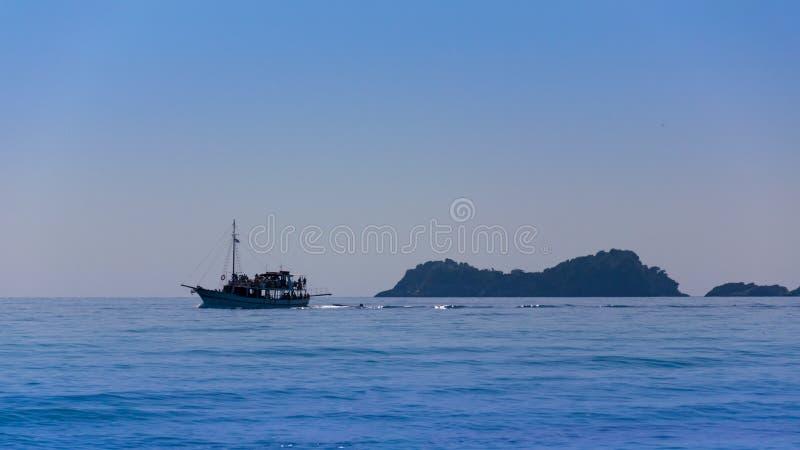 Velero en el mar Mediterráneo, con agua azul y las rocas vistas de lejos foto de archivo