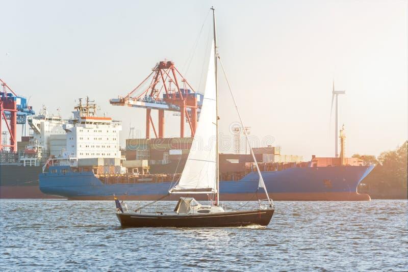 Velero en el río Elba en Hamburgo delante y del puerto de portacontenedores en el sol de igualación imagenes de archivo