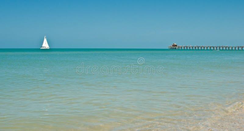 Velero en los mares tranquilos que se mueven hacia un embarcadero fotos de archivo