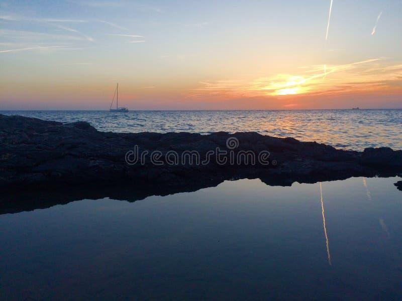 Velero en puesta del sol imagen de archivo libre de regalías