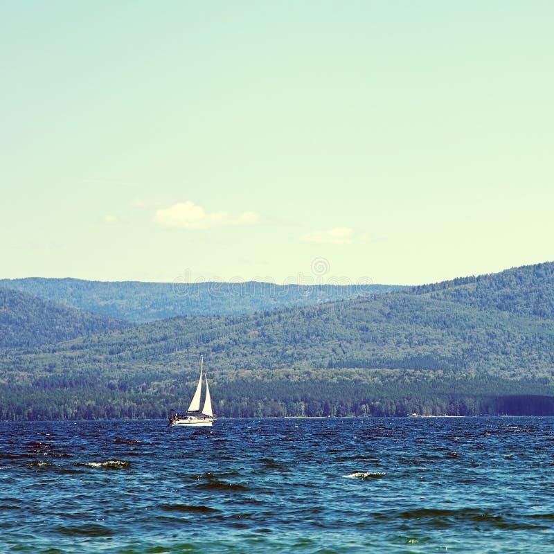 Velero en un lago de la monta?a en buen tiempo en un fondo del cielo azul imágenes de archivo libres de regalías