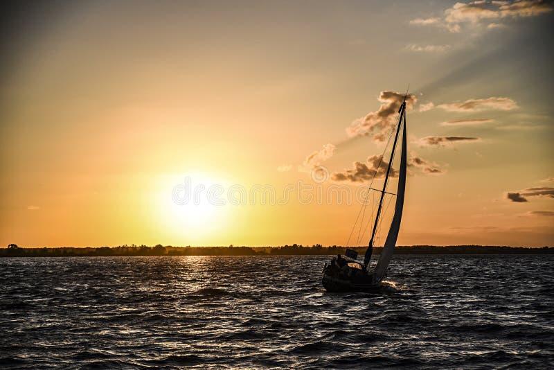 Velero en una bahía en la puesta del sol Szczecinski de Zalew, Polonia fotografía de archivo