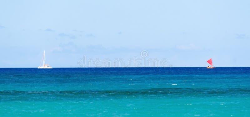 Veleros rojos y blancos en aguas entre la bahía de Wailalea y Hapuna imagen de archivo libre de regalías