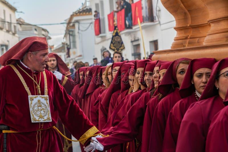 VELEZ-MALAGA, ESPAÑA - 25 DE MARZO DE 2018 gente que participa en la procesión conectada en una semana santa en una ciudad españo foto de archivo