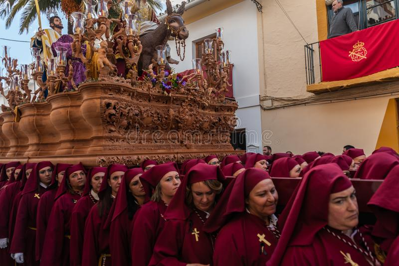 VELEZ-MALAGA, ESPAÑA - 25 DE MARZO DE 2018 gente que participa en la procesión conectada en una semana santa en una ciudad españo imagen de archivo