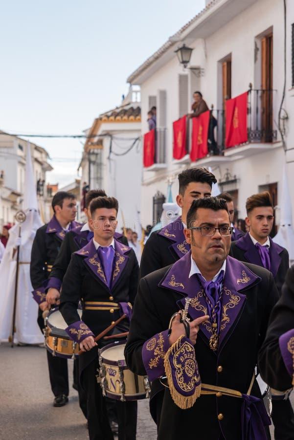 VELEZ-MALAGA, ESPAÑA - 25 DE MARZO DE 2018 gente que participa en la procesión conectada en una semana santa en una ciudad españo imagenes de archivo