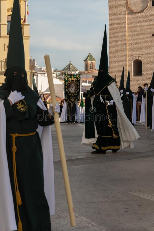 VELEZ-MALAGA, SPAIN - MARCH 29, 2018 People participating in the procession  in the Holy Week in a Spanish city royalty free stock photography