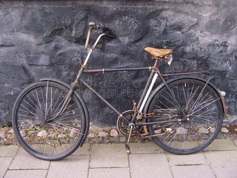 Velha bonito, vintage e bicicleta retro, datando from 1950 estacionou na passagem entre as casas velhas fixadas com corrente naug imagem de stock