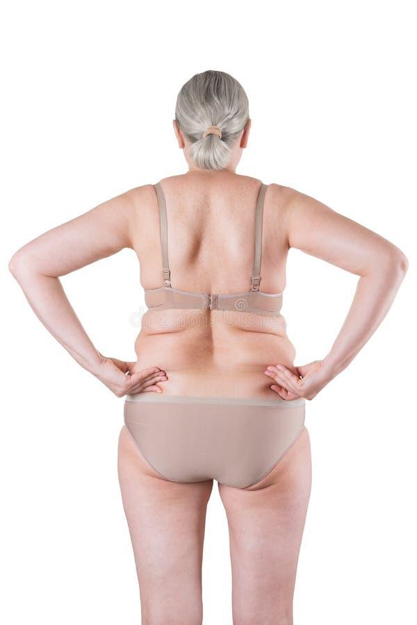 Velha gorda isolada em fundo branco, com excesso de peso na parte de trás com dobras de pele fotos de stock