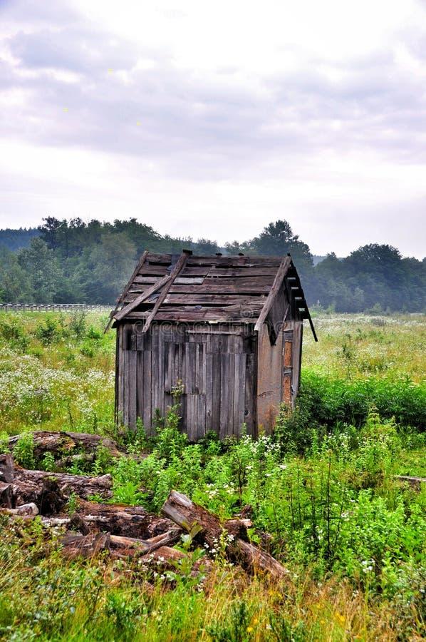 Velho abandonado destruído um celeiro em um campo verde imagens de stock royalty free
