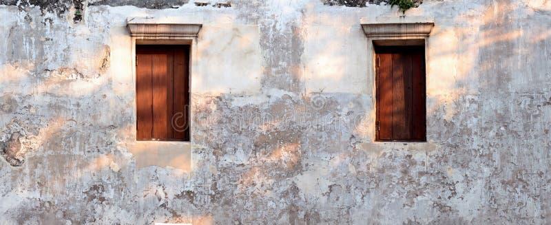 velho concreto a superfície de irregular parede para o fundo da textura, panorama largo, em janelas de madeira com noite de brilh fotografia de stock