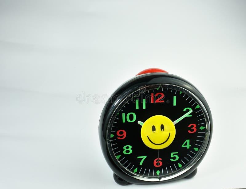 Velho despertador com face feliz sorridente isolada em fundo branco fotos de stock
