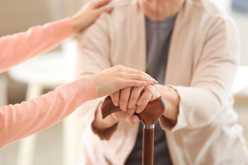 Velho e jovens mulheres que guardam as mãos na vara de passeio fotos de stock royalty free