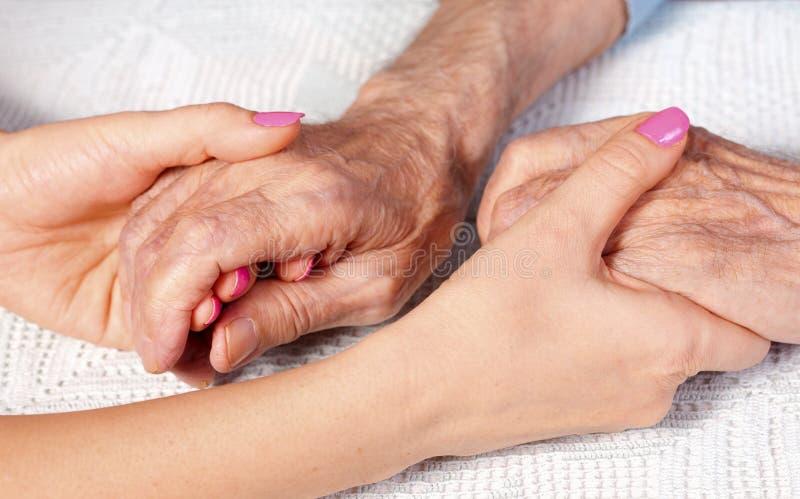Velho e jovens que guardam as mãos no fundo claro, close up O cuidado é em casa das pessoas idosas foto de stock royalty free