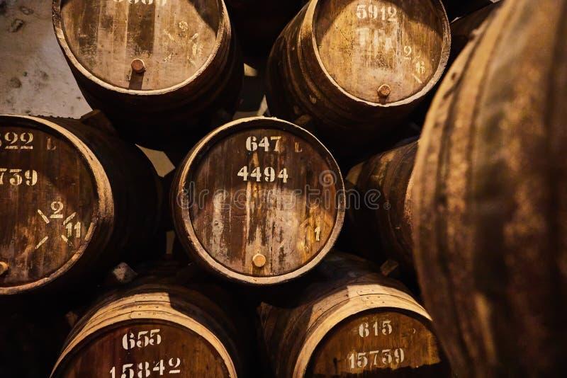 Velho envelheceu tambores de madeira tradicionais com vinho em um cofre-forte alinhado na adega fresca e escura em Itália, Porto, foto de stock royalty free