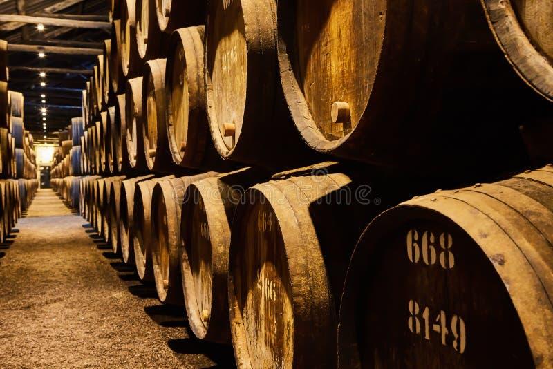 Velho envelheceu tambores de madeira tradicionais com vinho em um cofre-forte alinhado na adega fresca e escura em Itália, Porto, imagem de stock