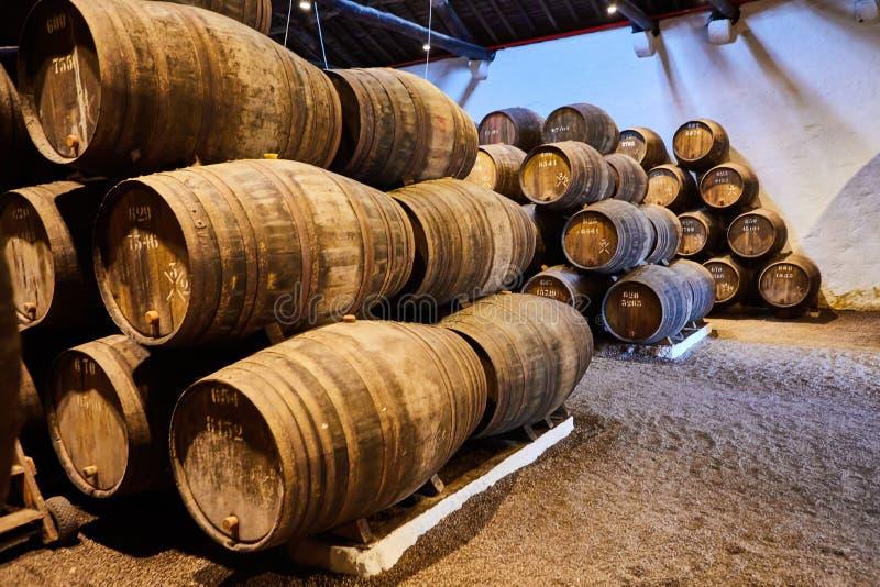 Velho envelheceu tambores de madeira tradicionais com vinho em um cofre-forte alinhado na adega fresca e escura em Itália, Porto, fotografia de stock