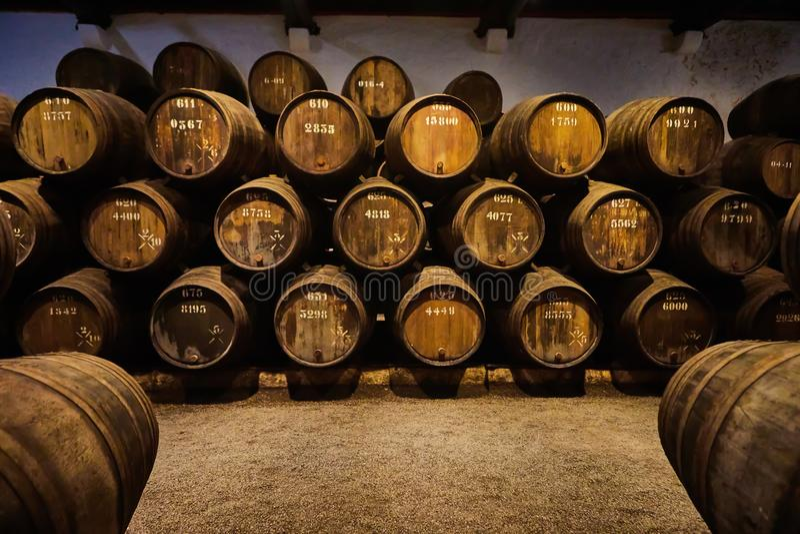 Velho envelheceu tambores de madeira tradicionais com vinho em um cofre-forte alinhado na adega fresca e escura em Itália, Porto, foto de stock