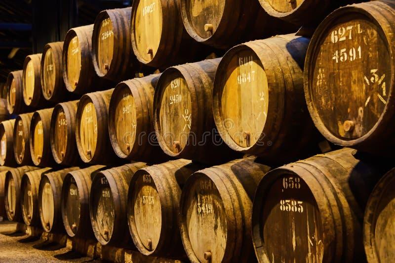 Velho envelheceu tambores de madeira tradicionais com vinho em um cofre-forte alinhado na adega fresca e escura em It?lia, Porto, imagem de stock
